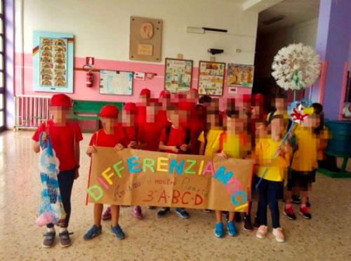 """Alunni della scuola elementare Don Bosco che mostrano un cartellone con scritta """"differenziamoci"""", in riferimento alla necessità di fare la raccolta differenziata."""